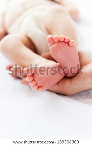 Tiny little feet. Close-up of father holding a tiny hand of his little baby
