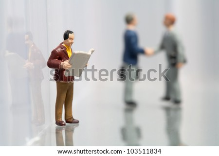 Tiny little miniature model of a man reading the newspaper while taking a break at work with two colleagues shaking hands in the background - stock photo