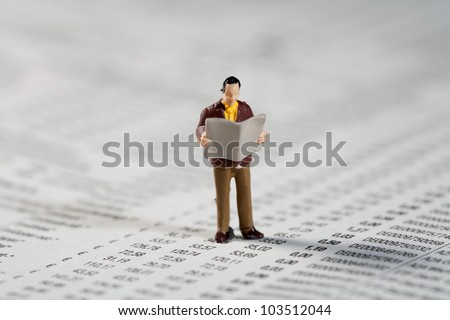 Tiny little model figurine of a private investor standing reading the financials and updated market reports in the paper while standing on a financial document - stock photo