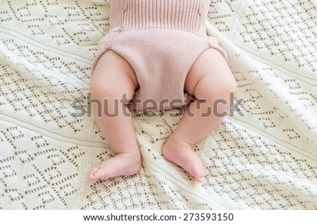Tiny little newborn daughter baby's feet in woolen shorts lying on the background of white woolen blanket on a bed at home, top view.  - stock photo