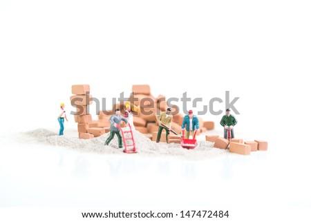 Tiny miniature people busy doing construction brickwork close up - stock photo