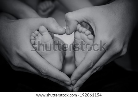 Tiny Newborn Baby`s feet being held by father's hand.