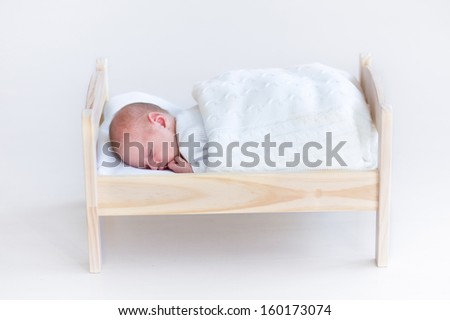 Tiny newborn baby sleeping in a toy crib under a white blanket - stock photo