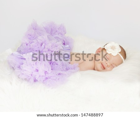 Tiny newborn baby sleeping on white blanket, wearing lilac tutu and flower headband. Dreamy smile on face.