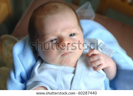 Tiny newborn boy is nestled in blankets of blue and yellow as he arrives at his home for the first time.  Eyes are open and a tiny hand rises as if to wave. - stock photo