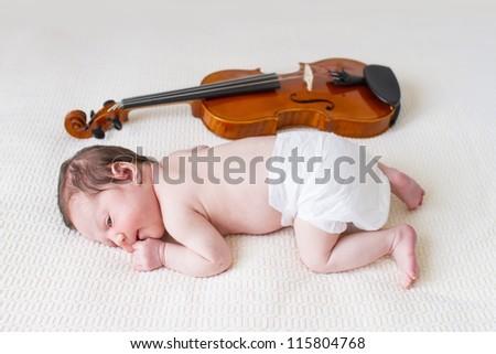 Tiny newborn girl lying next to a violin - stock photo