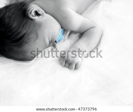 Tiny newborn sleeps in peace free of stress and worries.  He is laying on layers on netting in the corner of photo.