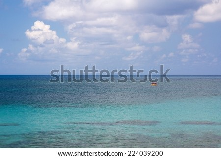 Tiny paddle boat in the vast Caribbean ocean. - stock photo