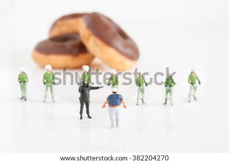 Tiny police in riot gear preventing an overweight man from reaching donuts a public health obesity concept selective focus on foreground figures