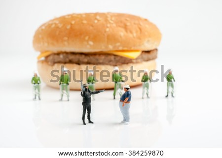 Tiny police preventing an overweight man from reaching a burger a public health obesity concept selective focus on foreground figures - stock photo