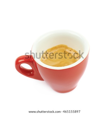 Tiny red ceramic cup filled with the espresso coffee isolated over the white background