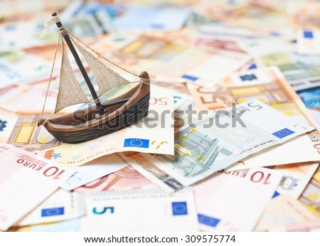 Tiny ship over the surface covered with the multiple euro bank notes, shallow depth of field composition - stock photo