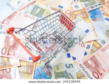 Tiny shopping cart over the surface covered with the multiple euro bank note bills - stock photo