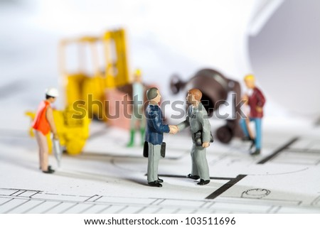Tiny toy model figures of tradesmen and workers in the construction industry with their equipment on a building site on a blueprint plan for a house design