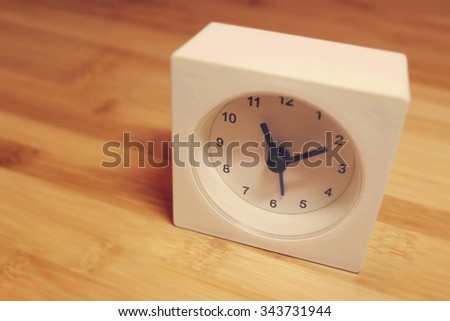Tiny white clock sitting on a work desk.  - stock photo