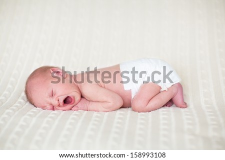 Tiny yawning newborn baby in a diaper sleeping on a knitted blanket - stock photo
