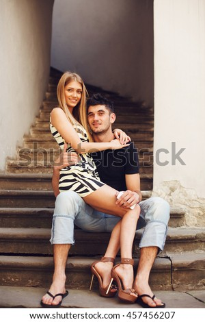 Tiny young lady sits on handsome boy's knee