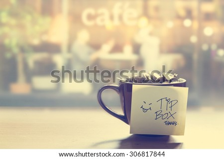 Tip box, coin in the coffee cup in cafe front of mirror, Vintage color and soft concept - stock photo