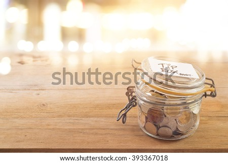 Tip box, coin in the glass jar in cafe front of mirror at night - stock photo