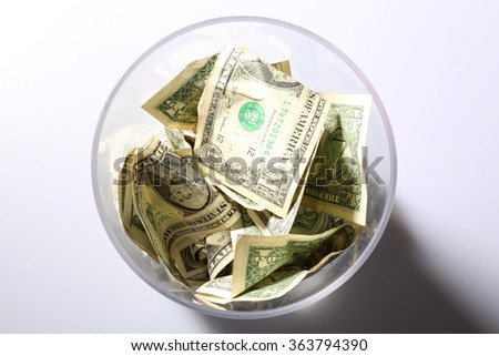 Tip Jar. Cash tips in a clear plastic Tip Jar. Tips are a token of appreciation for a Job Well Done for services. Tips are well appreciated by all who get them. Cash is King. - stock photo