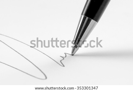 tip of a ballpen while drawing a line in light back