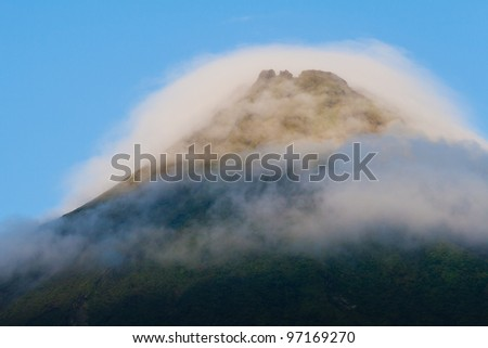 Tip of Arenal Volcano in morning light, surrounded by clouds - stock photo