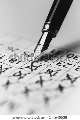 Tip of fountain pen marking date in calendar (b&w) (close-up) - stock photo