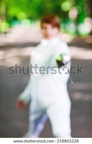 Tip of rapier held by fencer woman staying in park alley, shallow depth of field - stock photo