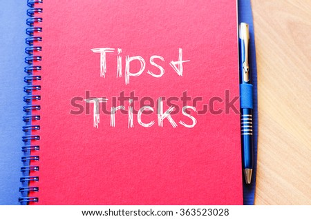 Tips and tricks text concept write on notebook with pen - stock photo