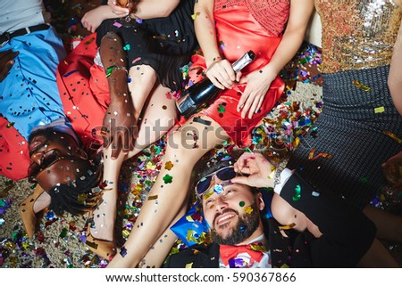 Tipsy multiethnic group of friends relaxing on floor with colorful confetti while celebrating holiday together