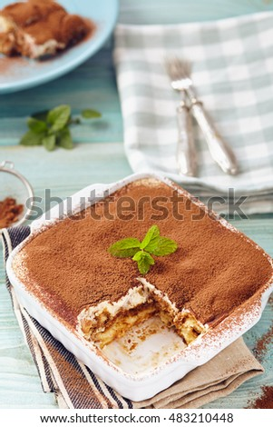 Tiramisu cake in an oven pan on a blue wooden  table with dishes and forks