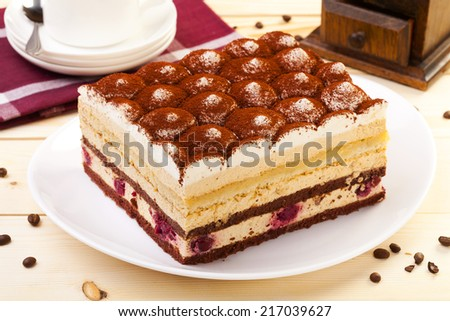 tiramisu cake on plate served with a cap of coffee