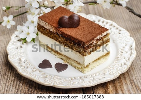 Tiramisu cake on white plate. Blossom apple branch in the background. Wooden background, selective focus. - stock photo