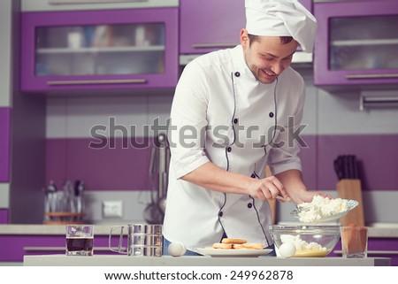 Tiramisu cooking concept. Portrait of smiling man in cook uniform making italian dessert in modern kitchen. Indoor shot - stock photo