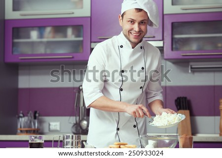 Tiramisu cooking concept. Portrait of smiling man in cook uniform making italian dessert in modern kitchen. Indoor shot - stock photo