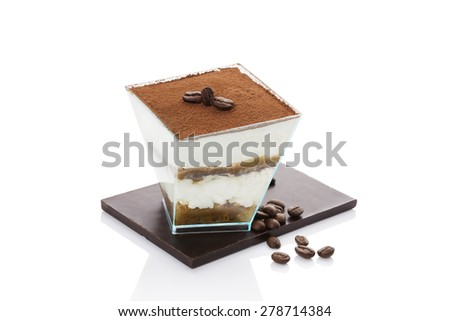 Tiramisu dessert on chocolate bar with roasted coffee beans isolated on white background. Italian sweet dessert concept. - stock photo