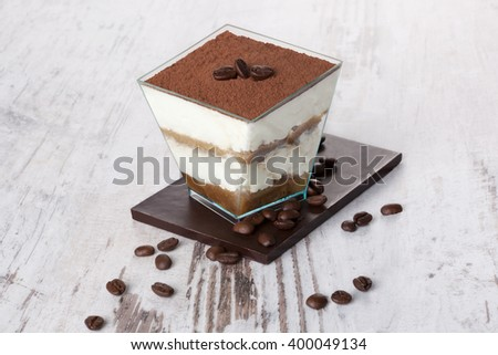 Tiramisu dessert with chocolate and coffee beans on white wooden textured table. Traditional tiramisu dessert, rustic, country style. - stock photo
