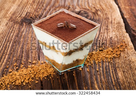 Tiramisu dessert with coffee beans and instant coffee on wooden textured table. Traditional tiramisu dessert, rustic, country style. - stock photo