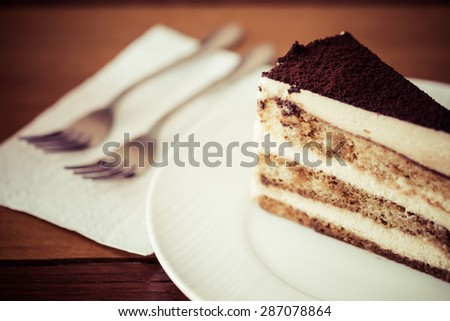 Tiramisu in the plate on the wooden background, process color - stock photo