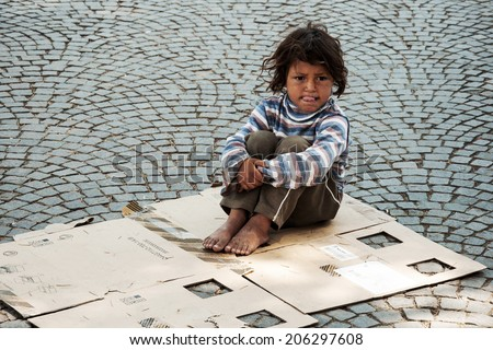 TIRANA, ALBANIA, MAY 14, 2010 - Unknown homeless kid sitting on the old box on the street in Tirana - stock photo
