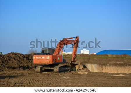 TIRASPOL, TRANSNISTRIA - 8 MAY: Orange excavator Hitachi  Zaxis near the construction site of the canyon at sunset in May 2016 in Tiraspol, Transnistria. - stock photo