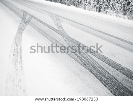 Tire marks weaving along a snow covered road. - stock photo