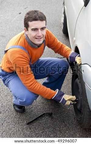 tire repairer changing a flat - stock photo