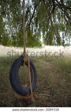 Charmant Tire Swing Hanging From A Willow Tree In The Backyard Of An Old Farm