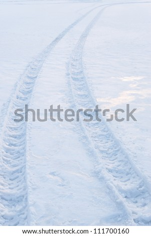 Tire trace on snow leaving to the horizon - stock photo