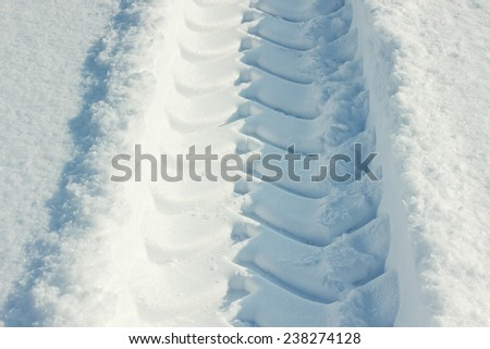 Tire tracks in fresh snow on a sunny day - stock photo