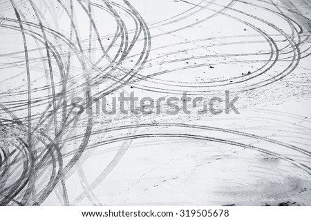 Tire tracks in snowy parking lot. - stock photo