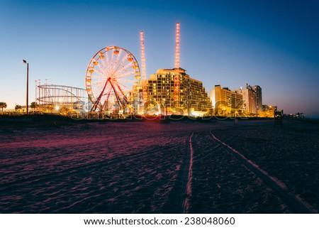 Tire tracks on the beach, rides and hotels at night, in Daytona Beach, Florida. - stock photo