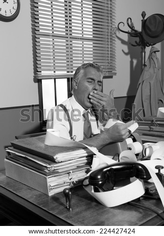 Tired accountant yawning and checking bills at his desk, vintage office. - stock photo