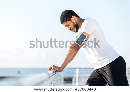 Tired african young sportsman listening to music from blank screen mobile phone outdoors - stock photo